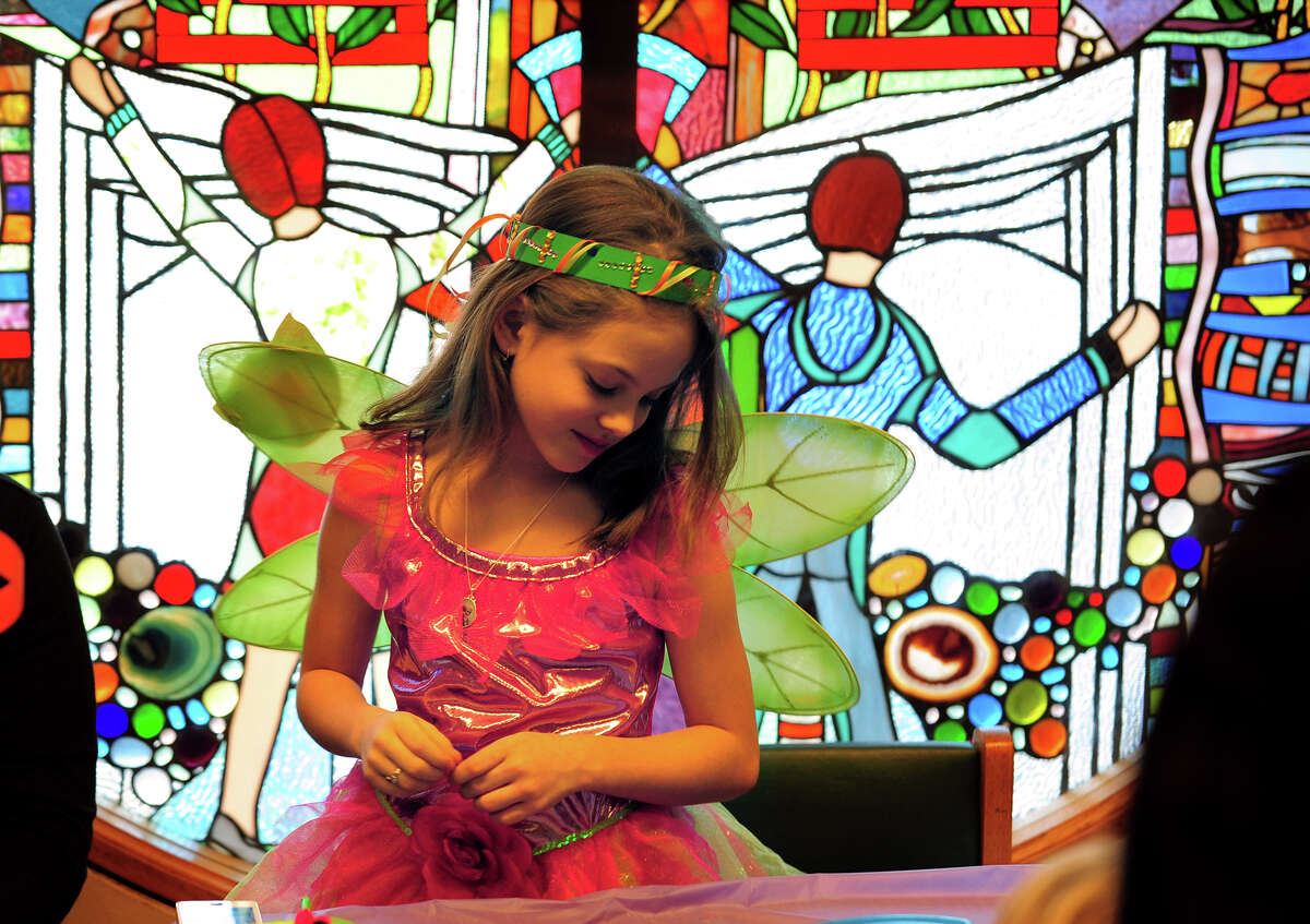 Riley Pihonak, 8, smiles after finishing her fairy costume, during Fairy Magic Party held at the Stratford Library in Stratford, Conn. on Saturday Jan. 17, 2015. Rainbow Magic Fairies is a popular children's book series by author Daisy Meadows. At the party, children are encouraged to dress up as one of their favorite fairies. Games and other fun activities were also held for them.