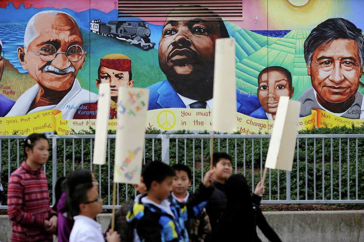 E.R. Taylor Elementary students walk past a mural during a march honoring the Rev. Martin Luther King Jr.