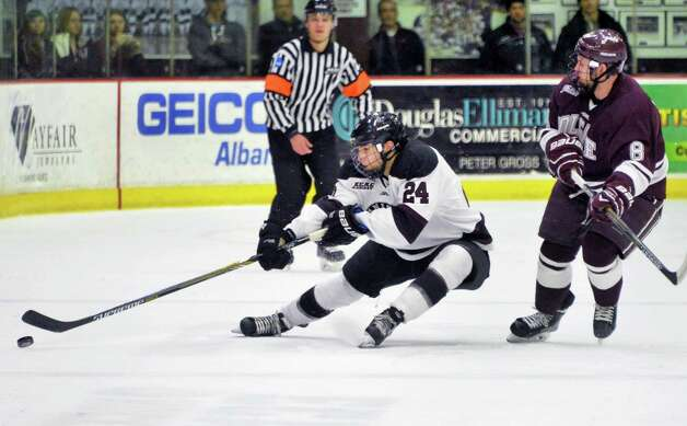 Union's #24 Sebastien Gingras reaches for the puck as  and Colgate's #8 Tyson Spink closes in during Saturday night's game  Jan. 17, 2015, in Schenectady, NY.  (John Carl D'Annibale / Times Union) Photo: John Carl D'Annibale / 00030185B