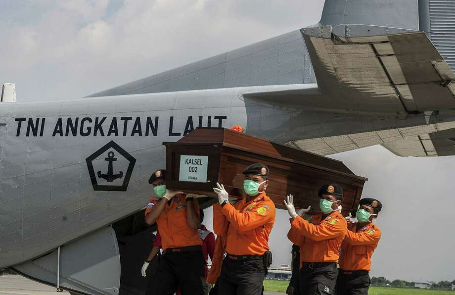 National disaster agency officers carry a coffin with the remains of a passenger of AirAsia Flight 8501 in Surabaya. Photo: Juni Kriswanto /Getty Images / AFP