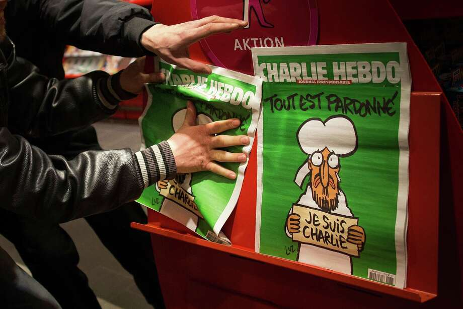 Two men grab the only two issues of the French satirical magazine Charlie Hebdo, the first published after the terror attacks in Paris, in a store in Berlin on Saturday. Photo: Carsten Koall /Getty Images / 2015 Getty Images