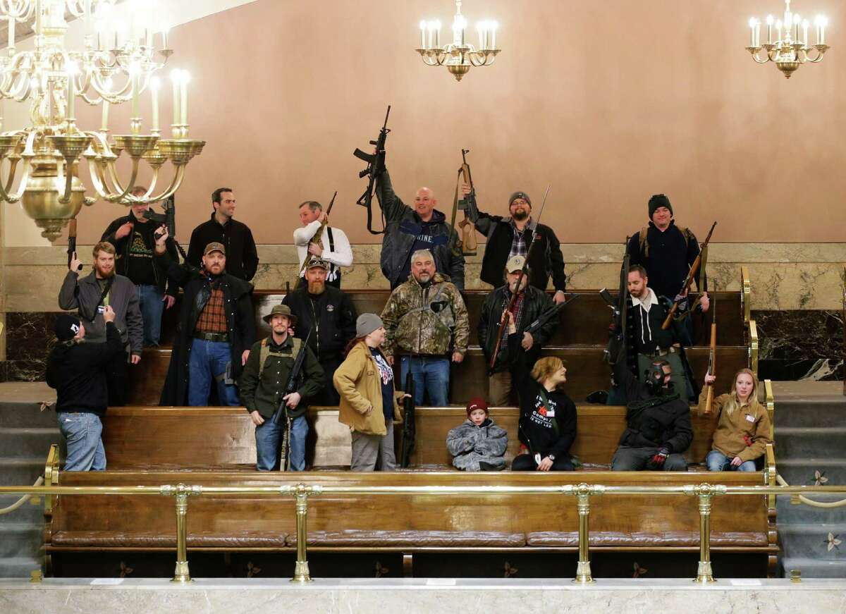 Gun owners display their weapons in the upper gallery of the House chambers, Thursday, Jan. 15, 2015, at the Capitol in Olympia, Wash. The House was not in session when this photo was taken, and members of the group went to the gallery following a protest outside the Legislative building in opposition to the state's Initiative 594, which requires - with only a few exceptions - background checks on all gun sales and transfers.