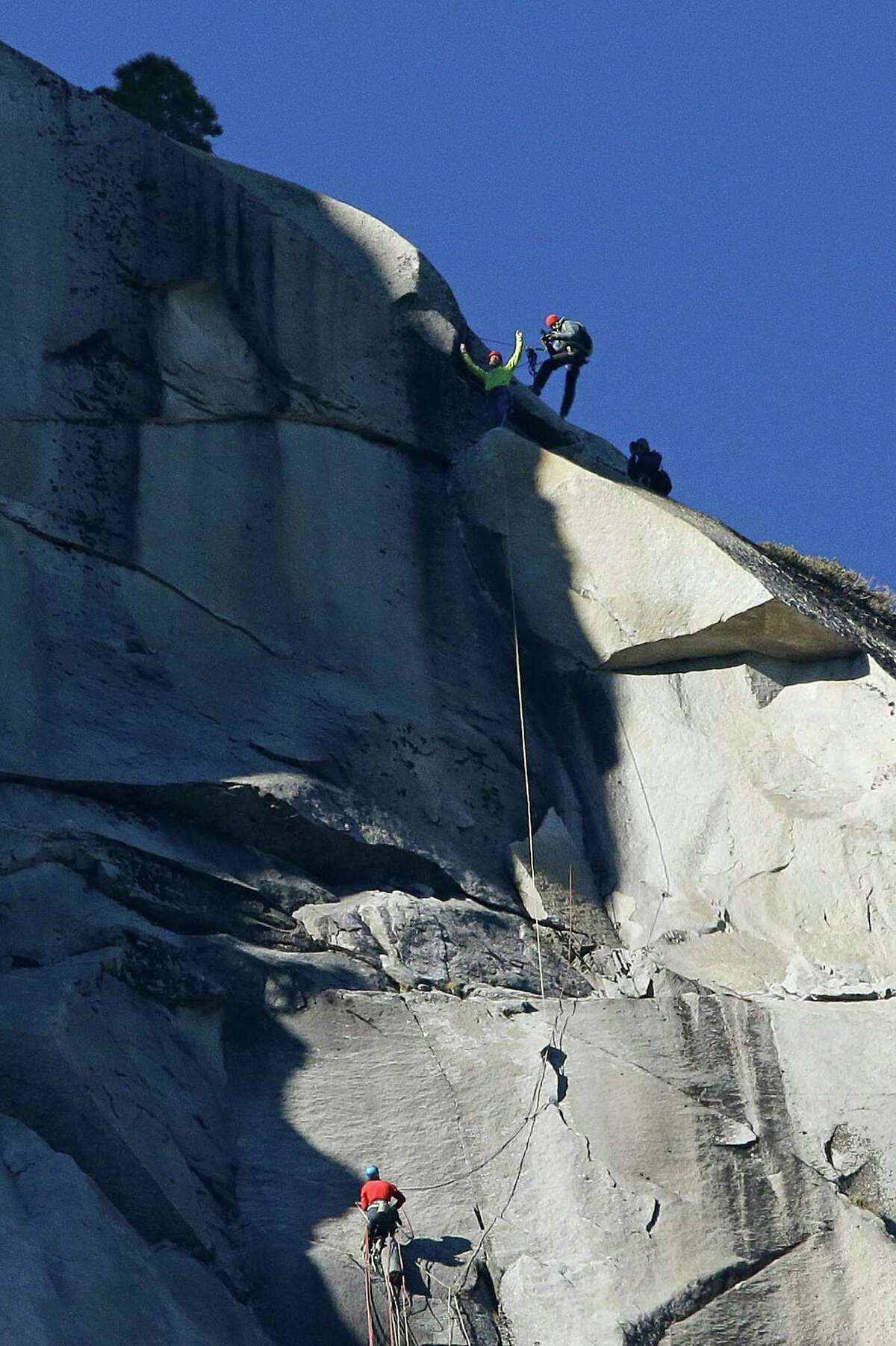 Tommy Caldwell, top, raises his arms after reaching the summit of El Capitan as Kevin Jorgeson, bottom, watches Wednesday, Jan. 14, 2015, as seen from the valley floor in Yosemite National Park, Calif. Caldwell and Jorgeson became the first to free-climb the rock formation's Dawn Wall. They used ropes and safety harnesses to catch them in case of a fall, but relied entirely on their own strength and dexterity to ascend by grasping cracks as thin as razor blades and as small as dimes.