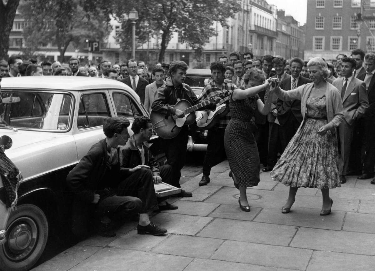 A group playing and jiving in the street at a Fifties fair in Soho, London.