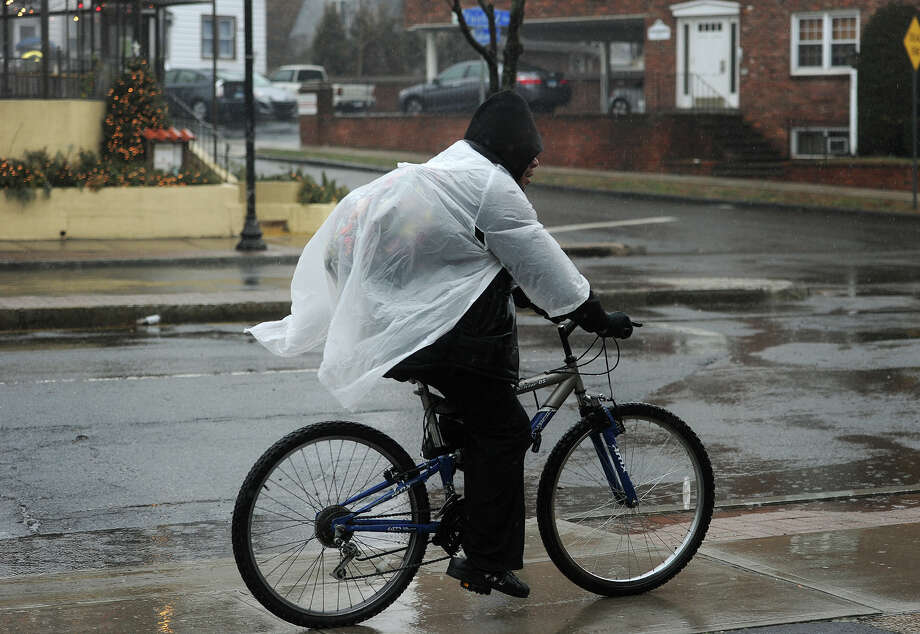 A cyclist attempts to keep dry from the rain along the Post Road in the Black Rock section of Bridgeport, Conn. on Sunday, January 18, 2015. Photo: Brian A. Pounds / Connecticut Post