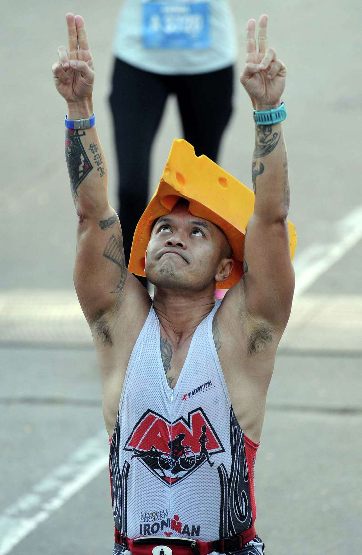 Marathoner Quoc Duong celebrates after crossing the finish line during the Houston Marathon, Sunday, January 18, 2015 in Houston.