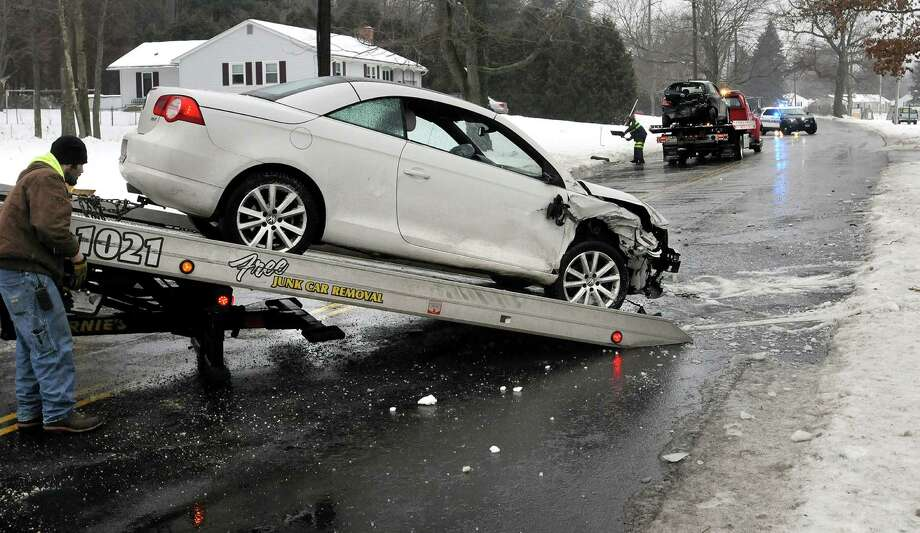 A tow truck driver, left, and first responders, behind, tend to the scene of a two-car accident Sunday, Jan. 18, 2015, in Easthampton, Mass. According to a first responder at the scene, there were no life-threatening injuries in the accident caused by icy driving conditions. (AP Photo/Daily Hampshire Gazette, Kevin Gutting) Photo: Kevin Gutting, MBR / Associated Press / Daily Hampshire Gazette