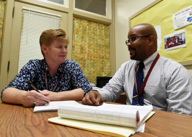 Kiante Jones, principal of Mont Pleasant Middle School works in his office with assistant principal Teresa Brown Wednesday morning, Oct. 22, 2014, at Mont Pleasant Middle School in Schenectady, N.Y.      (Skip Dickstein/Times Union) Photo: SKIP DICKSTEIN / 00029164A