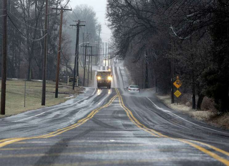 Trucks and cars drive slowly on an icy rural road Sunday, Jan. 18, 2015, near Newtown, Pa. Rain