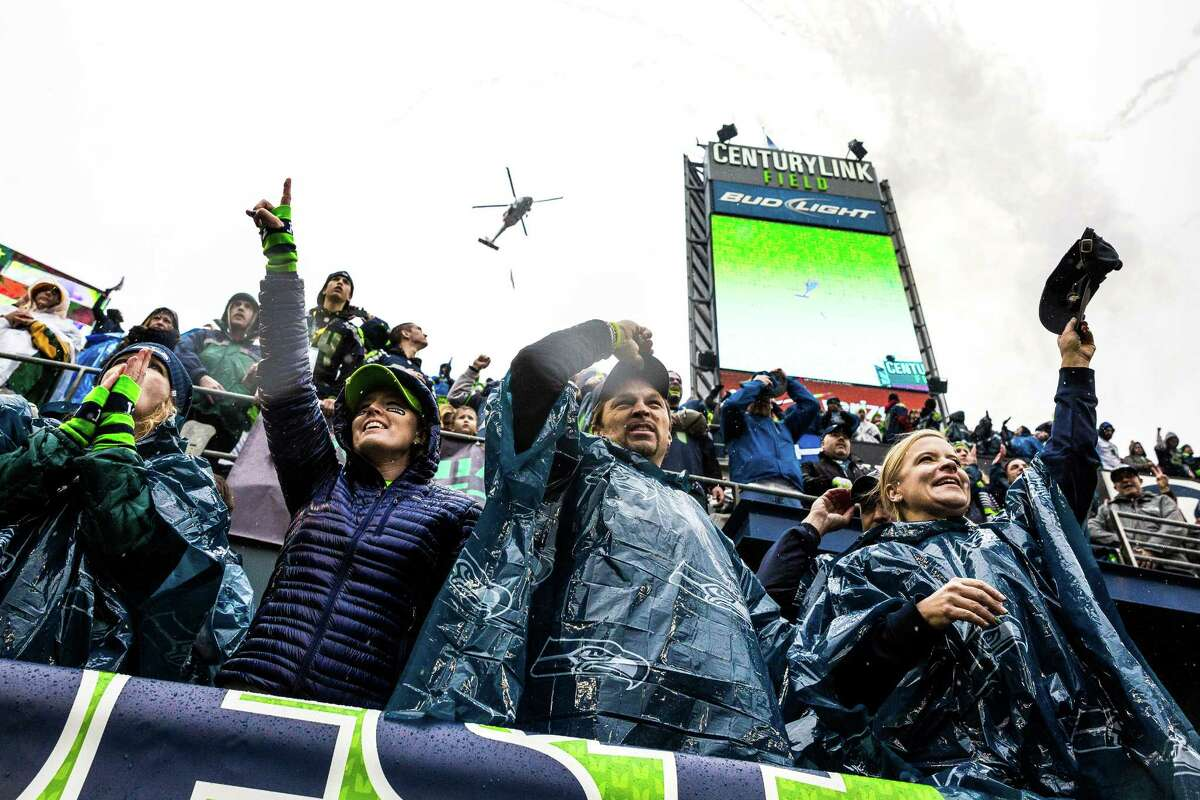 As a military helicopter executes a flyover overhead, Seahawks fans cheer on their home team before the NFC Championship game against the Green Bay Packers Sunday, January 18, 2015, at CenturyLink Field in Seattle, Washington.