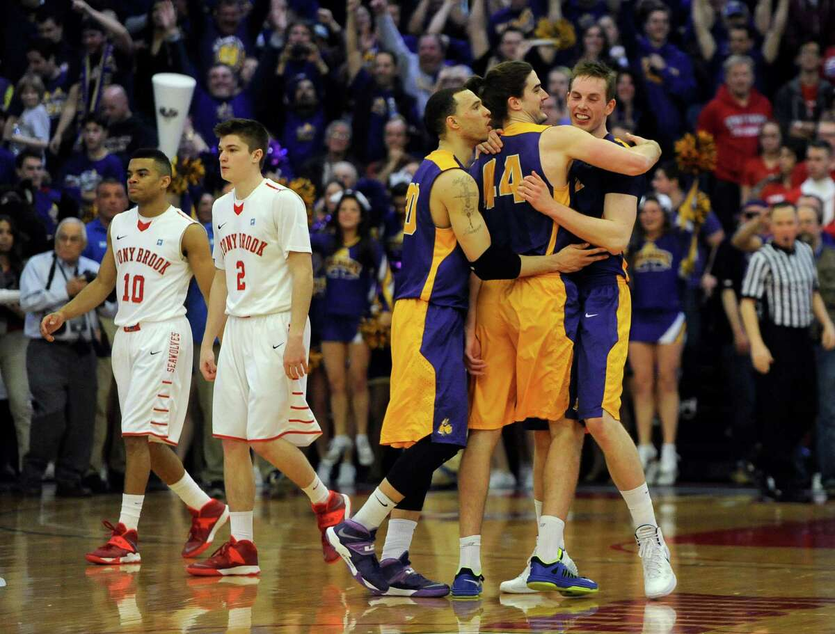 Albany's Gary Johnson (20), Sam Rowley (14), and Luke Devlin (11) celebrate as Stony Brook's Carson Puriefoy (10) and Kameron Mitchell (2) walk off the court after Albany beat Stony Brook 69-69 to win the championship of the America East Conference tournament NCAA college basketball game Saturday, March 15, 2014, in Stony Brook, N.Y. (AP Photo/Kathy Kmonicek) ORG XMIT: NYKK108
