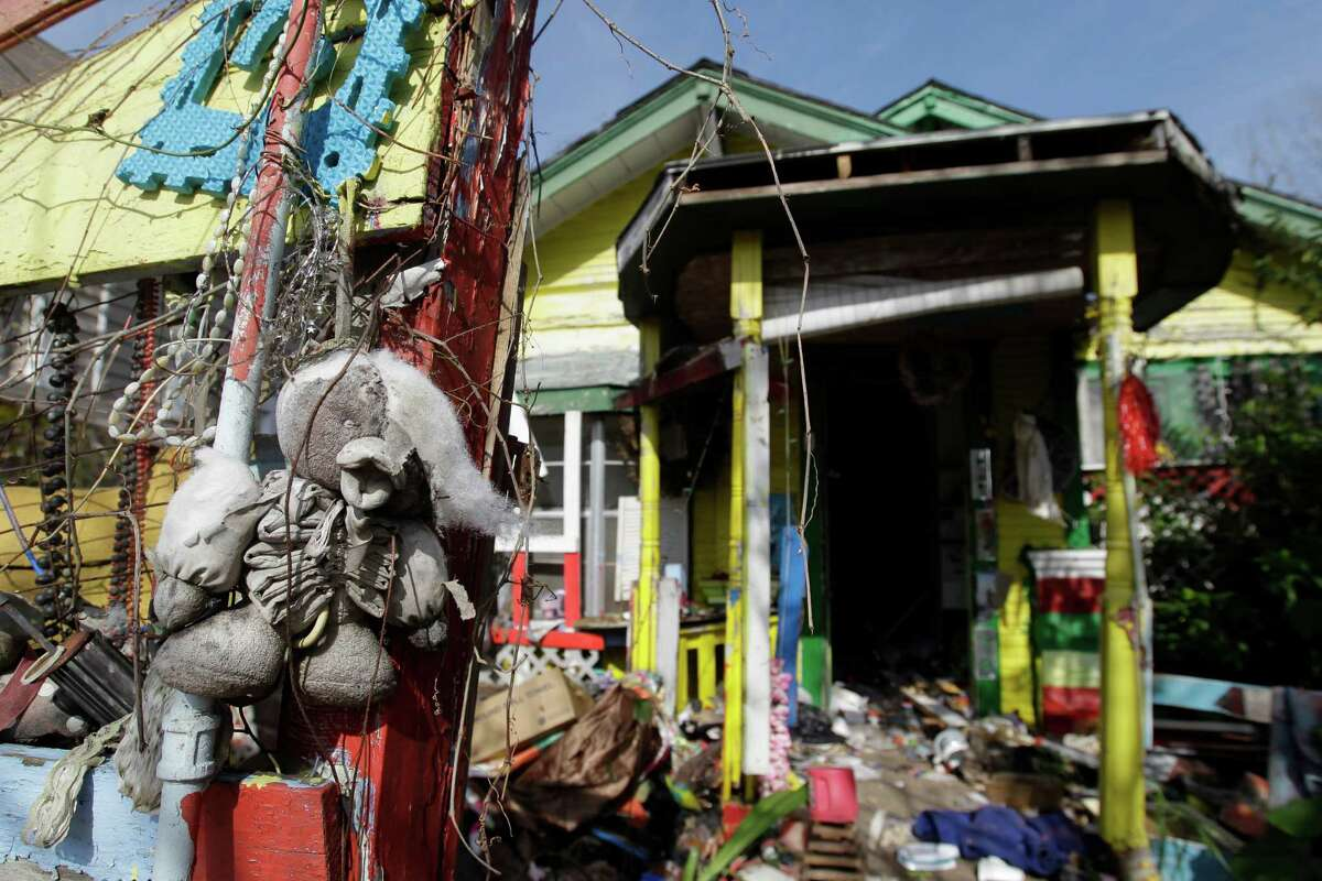 A weathered stuffed animal hangs on the fence at the home of Cleveland Turner, known as the Flower Man, shown Friday, Jan. 16, 2015, in Houston. The home will be torn down because it is in disrepair and full of mold. He filled his home and yard with re-imagined junk until his death in 2013.