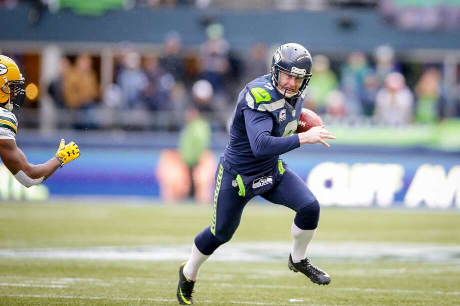 Seahawks' punter and kick-holder Jon Ryan rolls out during a fake kick in the third quarter and threw a touchdown pass to tackle Garry Gilliam in the NFC Championship game. Photo: SCOTT EKLUND, SEATTLEPI.COM