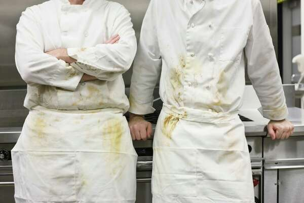 Dirty chefs leaning against stove.