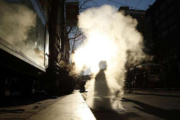 A pedestrian walks through steam from a sewer grate on Market Street in San Francisco, Calif. on Tuesday, January 13, 2015.