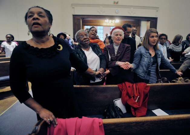 """Angela Dilworth-Gordon, left, of Guilderland, Shirley Readdean, second from left, of Schenectady, Pat Obrecht, third from left, of Schenectady, and Rachel Curtis, also of Schenectady, hold hands as they sing """"We Shall Overcome"""" at Mt. Olivet Baptist Church during a Martin Luther King, Jr. Celebration on Sunday, Jan. 18, 2015, in Schenectady, N.Y.  Readdean, Obrecht and Curtis are colleagues at the Schenectady Inner City Ministry.  This year's event was dedicated in remembrance of Rev. Eloise Frazier, the founder of the Schenectady County Human Rights CommissionOs Martin Luther King,Jr. Coalition.  Rev. Frazier passed away in October.  (Paul Buckowski / Times Union) Photo: Paul Buckowski / 00030152A"""