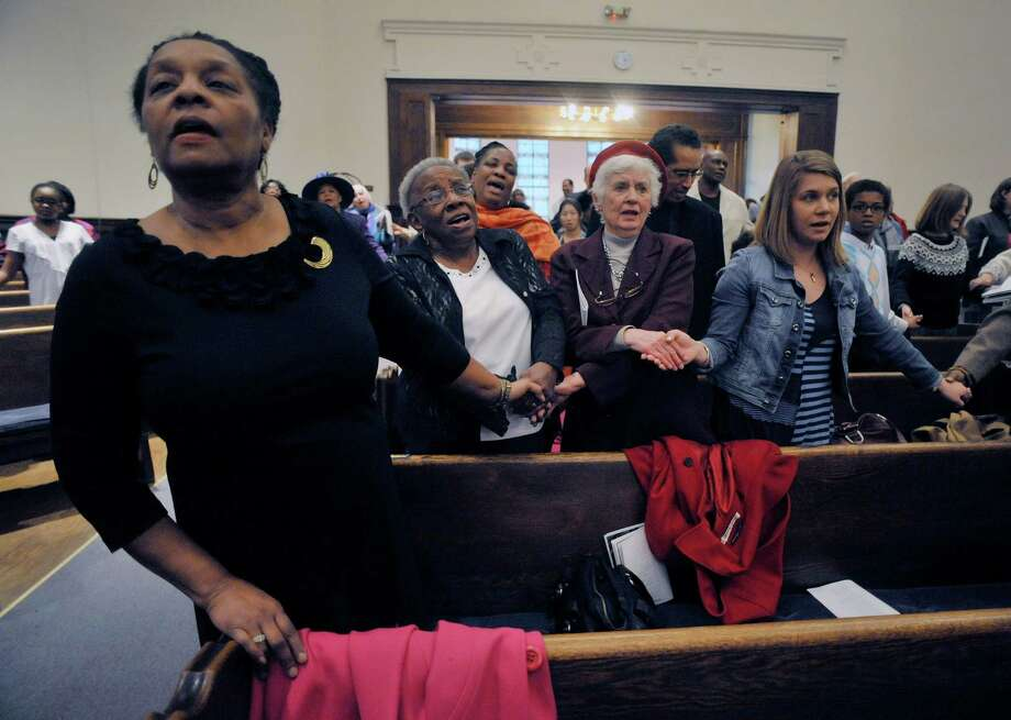 "Angela Dilworth-Gordon, left, of Guilderland, Shirley Readdean, second from left, of Schenectady, Pat Obrecht, third from left, of Schenectady, and Rachel Curtis, also of Schenectady, hold hands as they sing ""We Shall Overcome"" at Mt. Olivet Baptist Church during a Martin Luther King, Jr. Celebration on Sunday, Jan. 18, 2015, in Schenectady, N.Y.  Readdean, Obrecht and Curtis are colleagues at the Schenectady Inner City Ministry.  This year's event was dedicated in remembrance of Rev. Eloise Frazier, the founder of the Schenectady County Human Rights CommissionOs Martin Luther King,Jr. Coalition.  Rev. Frazier passed away in October.  (Paul Buckowski / Times Union) Photo: Paul Buckowski / 00030152A"