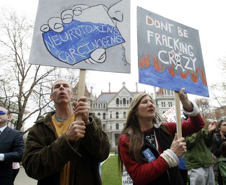 Mike Shuster, left, and Lisa Zaccaglini, both of Sharon Springs, N.Y., hold signs during a rally against hydraulic fracturing for natural gas in the Marcellus Shale region of the state, at the Capitol in Albany, N.Y., on Monday, April 11, 2011. (AP Photo/Mike Groll) Photo: Mike Groll, Associated Press