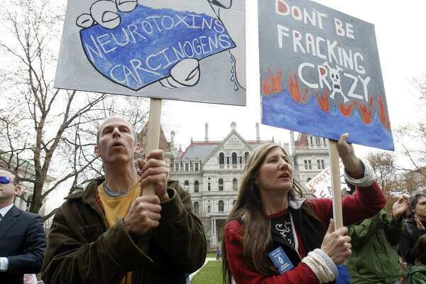 Mike Shuster, left, and Lisa Zaccaglini, both of Sharon Springs, N.Y., hold signs during a rally against hydraulic fracturing for natural gas in the Marcellus Shale region of the state, at the Capitol in Albany, N.Y., on Monday, April 11, 2011. (AP Photo/Mike Groll)