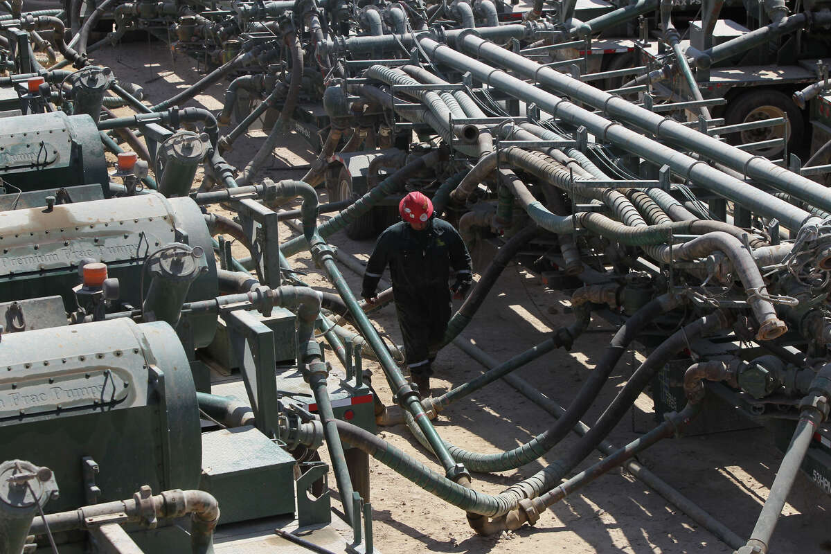 An oil worker walks pass the manifold (right) and frac pumps (left) at a Chesapeake Energy hydraulic fracturing operation near Carrizo Springs, Texas Thursday May 5, 2011. Hydraulic fracturing is a method of removing oil and gas from rock formations such as the Eagle Ford shale formation in south central Texas. JOHN DAVENPORT/jdavenport@express-news.net