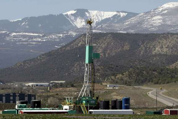 FILE - In this April 22, 2008 file photo, a natural gas well pad sits in front of the Roan Plateau near Rifle, Co. The director of the Colorado Oil and Gas Conservation Commission, David Neslin, said Monday, Dec. 5, 2011, that requiring drilling companies to publicly disclose what chemicals they use in hydraulic fracturing is only one tool for protecting public health and the environment. The comment was made during a hearing regarding a proposal to require public disclosures of fracking fluids that aren't trade secrets. More than 100 people packed the hearing.  (AP Photo/David Zalubowski, File)