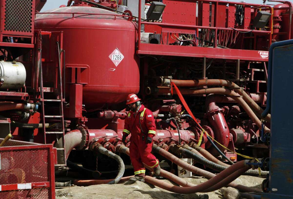 FILE- In this photograph taken April 15, 2009, an unidentified worker steps through the maze of hoses being used at a remote fracking site being run by Halliburton for natural-gas producer Williams in Rulison, Colo.