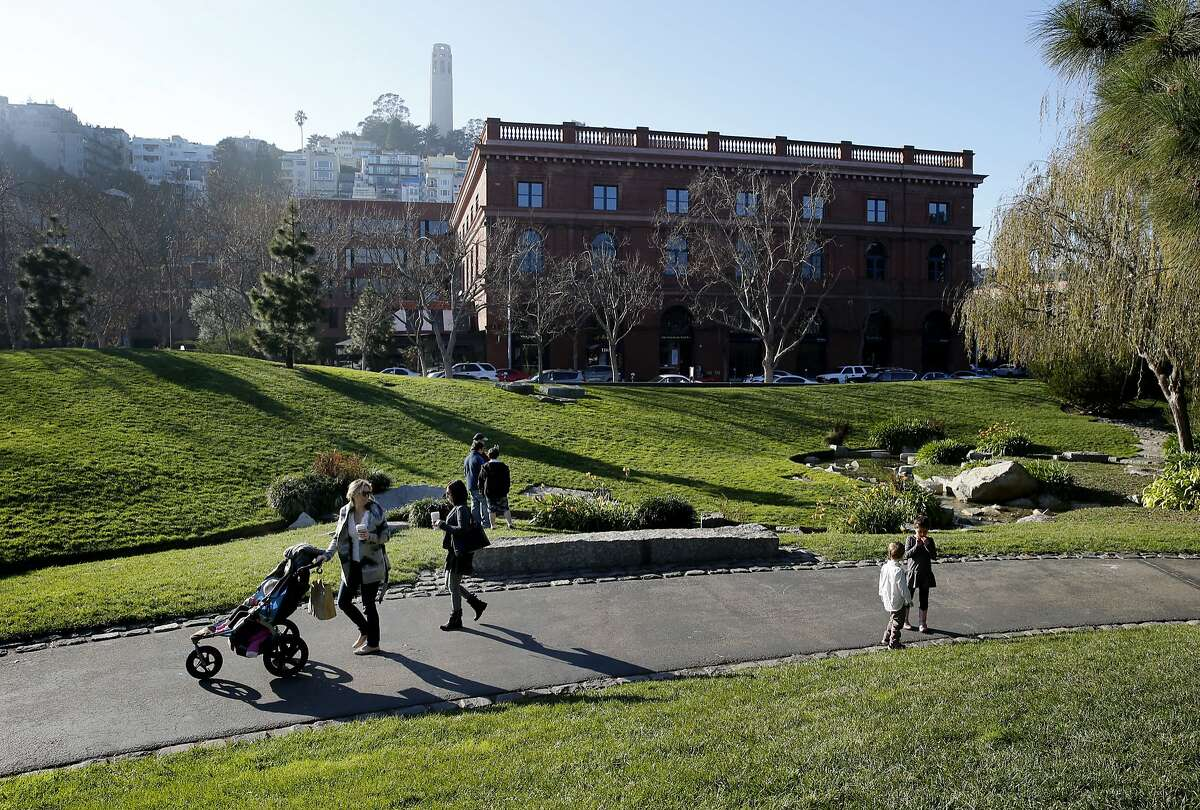 Pedestrians enjoy the sunny weather at Levi Plaza in San Francisco on Sunday, Jan. 18, 2015.