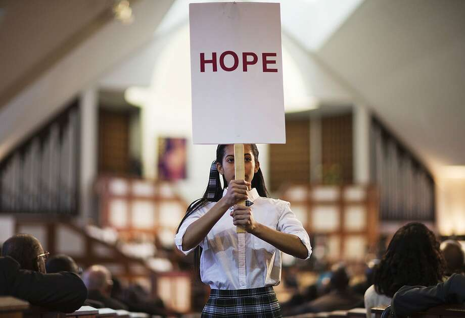 Jaiya Smith carries a sign down the aisle during a service honoring Rev. Martin Luther King Jr. at Ebenezer Baptist Church, where King preached, Monday, Jan. 19, 2015, in Atlanta. (AP Photo/David Goldman) Photo: David Goldman, Associated Press
