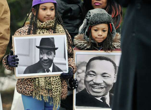 Icesis Hinkson-Serrano, left, 10, and her brother Mi-Son Hinkson-Serrano, 7, hold photographs of Martin Luther King, Jr. at the King Monument in Lincoln Park during a wreath laying ceremony following the Dr. Martin Luther King, Jr. Holiday Memorial Observance at the Empire State Plaza Convention Center on Monday, Jan. 19, 2015, in Albany, N.Y.   (Paul Buckowski / Times Union) Photo: Paul Buckowski / 00030151A