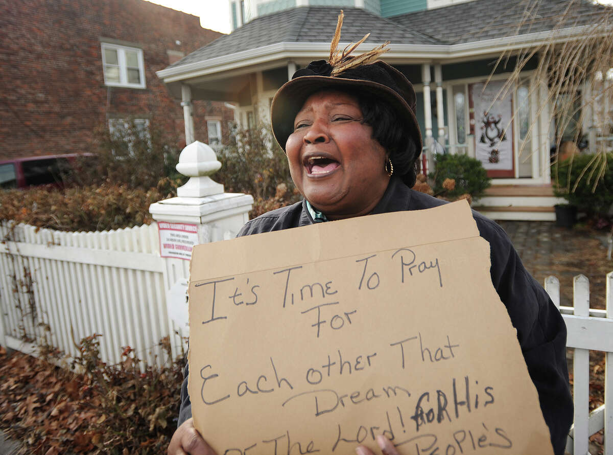 Gloria Brown cheers on the annual Martin Luther King, Jr. Day march outside her home on Hollister Avenue in Bridgeport, Conn. on Monday, January 19, 2015.