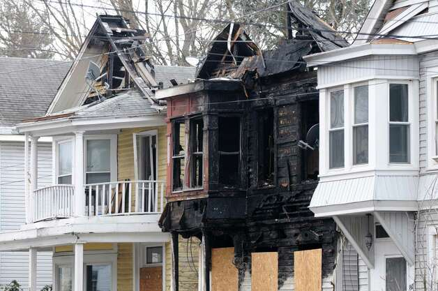 The scene of a fire which struck 809 Second Ave., and two adjacent buildings, early Sunday morning is secured by barricades Monday, Jan. 19, 2015, in north Troy, N.Y. The city is creating an arson task force and boosting patrols after another fire in a vacant Lansingburgh building stoked fears that a serial arsonist is on the loose. (Will Waldron/Times Union) Photo: WW