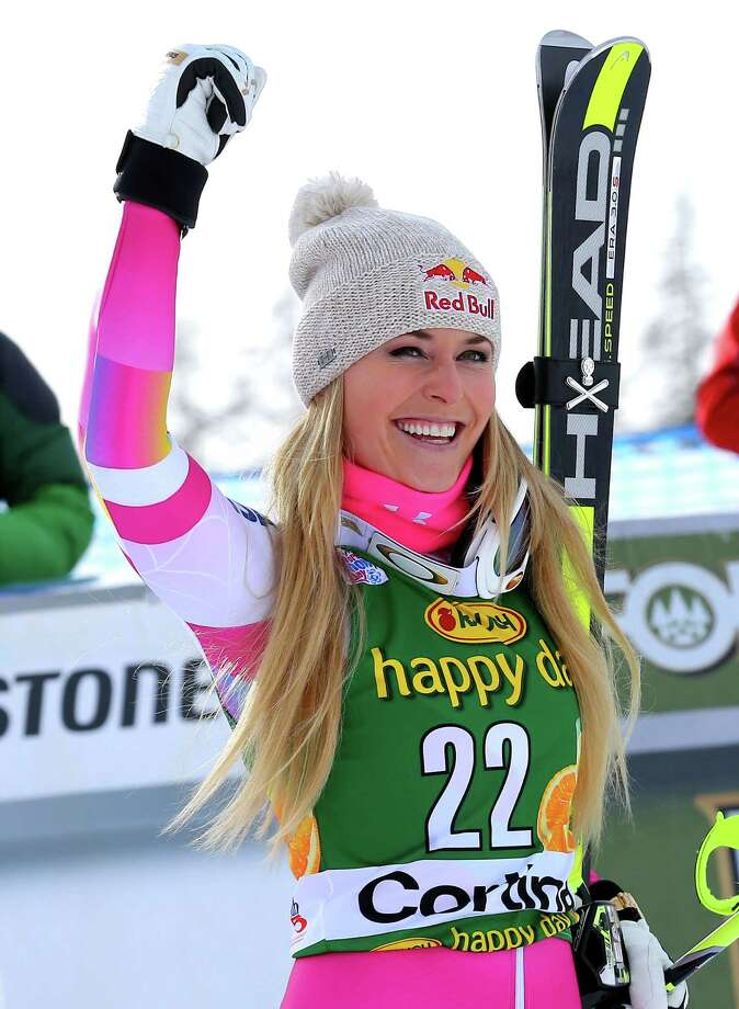 Lindsey Vonn celebrates after winning an alpine ski, women's World Cup super-G, in Cortina d'Ampezzo, Italy, Monday, Jan. 19, 2015. Lindsey Vonn won a super-G Monday for her record 63rd World Cup victory and celebrated with an embrace from a surprise visitor, boyfriend Tiger Woods. The American broke Annemarie Moser-Proell's 35-year-old record of 62 World Cup wins with a flawless run down the Olympia delle Tofane course, finishing 0.85 ahead of Anna Fenninger of Austria. (AP Photo/Armando Trovati) Photo: Armando / Associated Press / AP