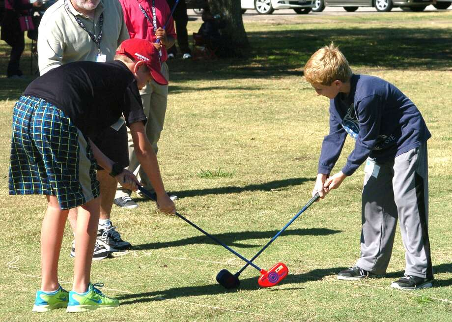 The Quail Valley Golf Club has a First Tee program for the children in the community.   Left, Tyler Jackson, 10, and Liam Meyerson, 9, use their clubs to try and gain control of the ball in the game of golf hockey. Photo: Eddy Matchette, Freelance / Freelance