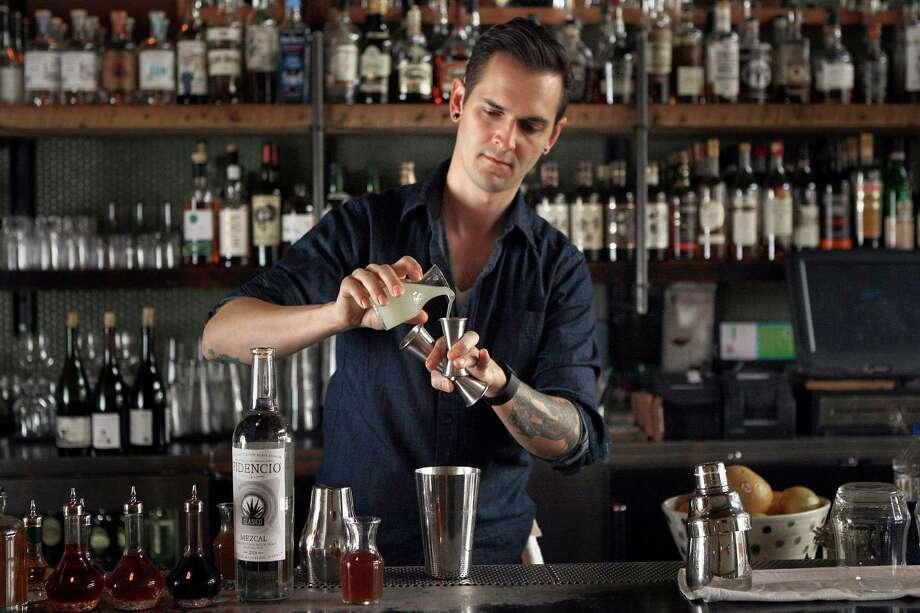 Bar manager Chris Lane mixes an Old Golden cocktail at Ramen Shop, a blend of mezcal, lemon, honey, ginger and sage. Sake is not on the menu. Photo: Liz Hafalia / The Chronicle / ONLINE_YES