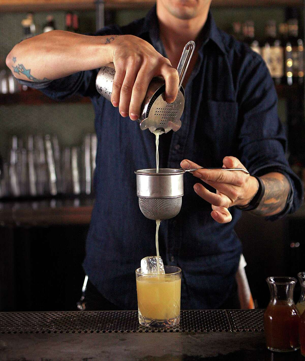 Bar manager Chris Lane mixes an Old Golden cocktail, a blend of mezcal, lemon, honey, ginger and sage, at the Ramen Shop in Oakland.