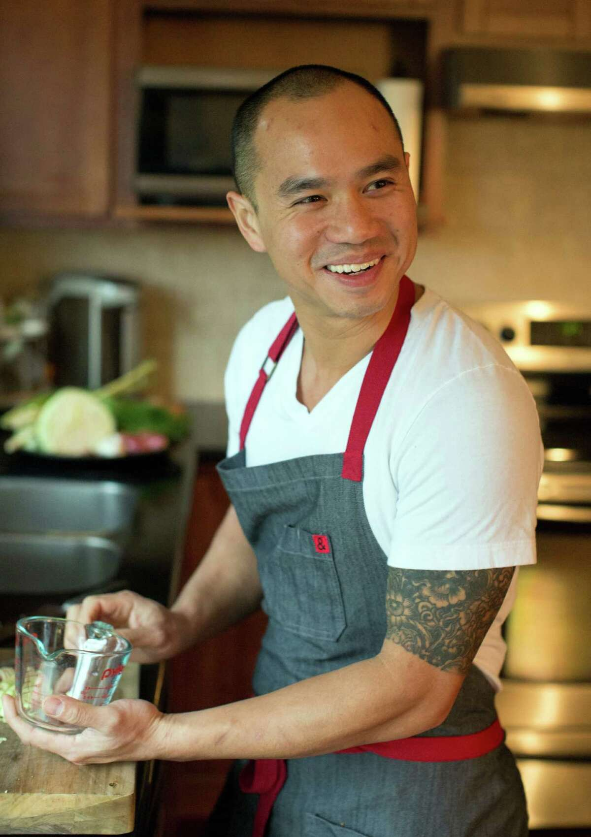 James Syhabout makes Laotian chicken stew at his home in Oakland.