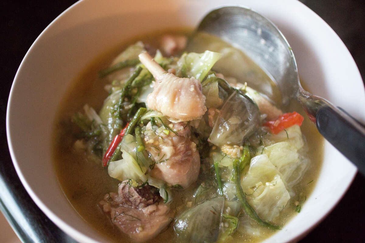 James Syhabout dishes up his Laotian chicken stew that he made at his home in Oakland.