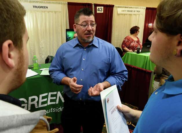 Eric Gohra of Trugreen speaks with job seekers during the Times Union Job Fair Monday morning, Jan. 19, 2015, at the Albany Marriott Hotel in Colonie, N.Y.    (Skip Dickstein/Times Union) Photo: SKIP DICKSTEIN / 00030245A