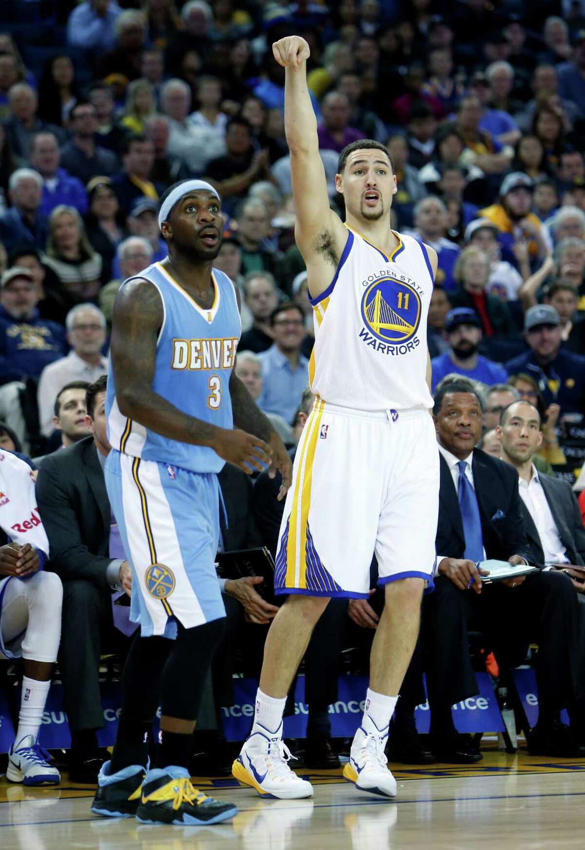 Klay Thompson signals watches his successGolden State Warriors' Klay Thompson and Denver Nuggets' Ty Lawson watch Thompson's successful 3-pointer in 2nd quarter during NBA game at Oracle Arena in Oakland, Calif. on Monday, January 19, 2015.