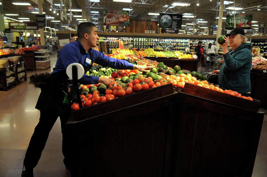 Produce Manager Gamaliel Franco, left, helps a customer with her selection of avocados at the Kroger store at 24350 Kuykendahl in Spring on Wednesday. The store opened last year. Photo: Jerry Baker, Freelance