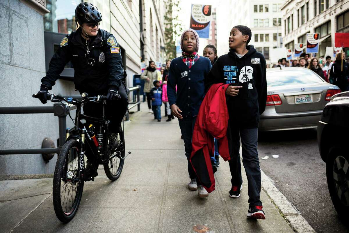 Kameron Port, right, joined by Khaim Vassar, center, take to the sidewalk to have a friendly chat with Officer R. Martinez, left, during the 33rd annual
