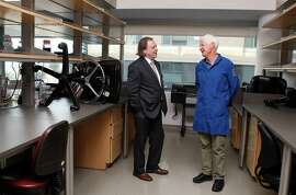 Alan Ashworth (left), director of the UCSF cancer center, con fers with pediatric cancer research specialist Kevin Shannon.