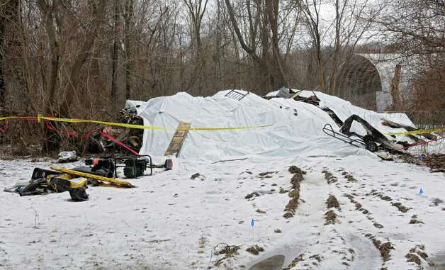 Tarps cover what remains of Colonie EMS worker Dave Plouff's house Monday, Jan. 19, 2015, in Watervliet, N.Y. Plouff's house was burned to the ground in December. The community has since raised over $50,000 for Dave. He's hoping to rebuild the home in the same spot. (Lori Van Buren / Times Union) Photo: Lori Van Buren / 00030259A