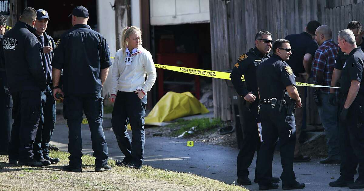 San Antonio police officers investigate the scene of a double fatality shooting behind the house in the 400 block of Linda Drive.