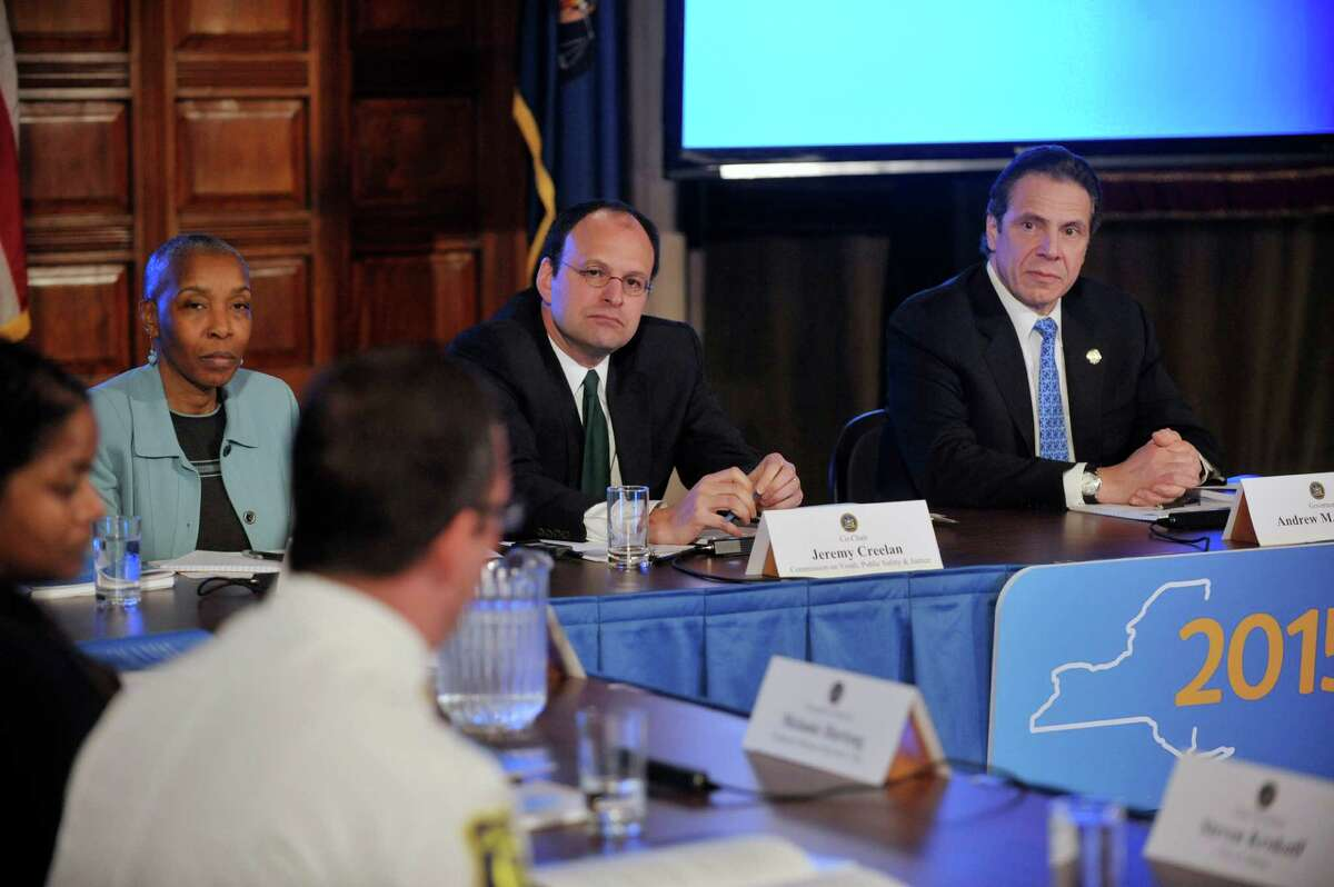 Commission on Youth, Public Safety and Justice co-chairs, Soffiyah Elijah, left, and Jeremy Creelan, center, along with Governor Andrew Cuomo, right, listen as commission member, Steven Krokoff, Albany Chief of Police, addresses the group during a meeting at the Capitol on Monday, Jan. 19, 2015, in Albany, N.Y. (Paul Buckowski / Times Union)
