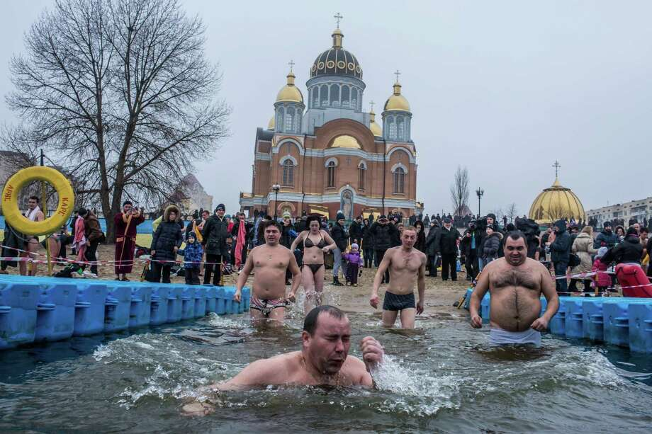 Orthodox Christians bathe in the Dnieper River in front of Holy Protection Cathedral for Epiphany on January 19, 2015 in Kiev, Ukraine. The holiday celebrates the baptism of Jesus for Orthodox Christians, who themselves plunge into the icy water to symbolically wash away their sins on a day when it is believed that all water becomes holy. Photo: Brendan Hoffman, Getty Images / 2015 Getty Images