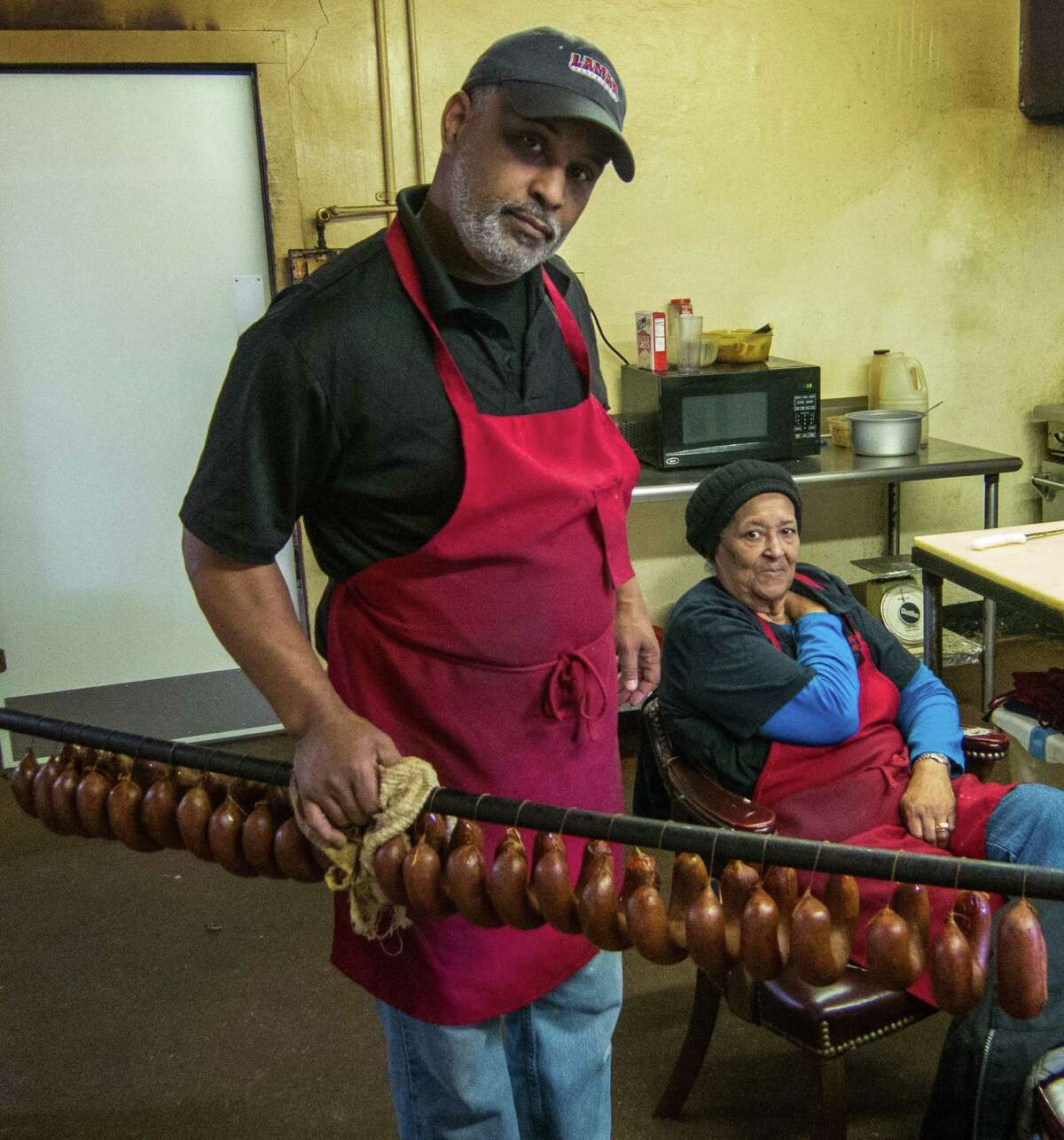George Gerard holds a rack of sausages as his mother, Marie Gerard, sits in the background at Gerard's Bar-B-Que.