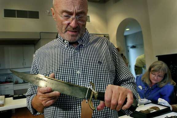 Phil Collins holds a Bowie knife that belonged to Jesse Robinson who fought under Jim Bowie at the Battle of Concepcion and the Siege of Bexar on Tuesday, Oct. 28, 2014 in San Antonio.  Collins has handed over his vast collection of artifacts related to the Battle of the Alamo and the Texas Revolution to the state of Texas.  Collins donated what's considered the world's largest private collection of Alamo artifacts. It includes a fringed leather pouch and a gun used by Davy Crockett and Jim Bowie's legendary knife.  (AP Photo/The San Antonio Express-News, Bob Owen)  RUMBO DE SAN ANTONIO OUT; NO SALES