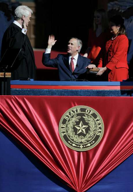 Incoming Texas Gov. Greg Abbott, center, is sworn in to office by Chief Justice Nathan Hecht, left, as Abbott's wife, Cecilia, stands at right, Tuesday, Jan. 20, 2015, in Austin, Texas. Abbott is the first Texas governor to use a wheelchair. (AP Photo/Eric Gay) Photo: Eric Gay, Associated Press / AP