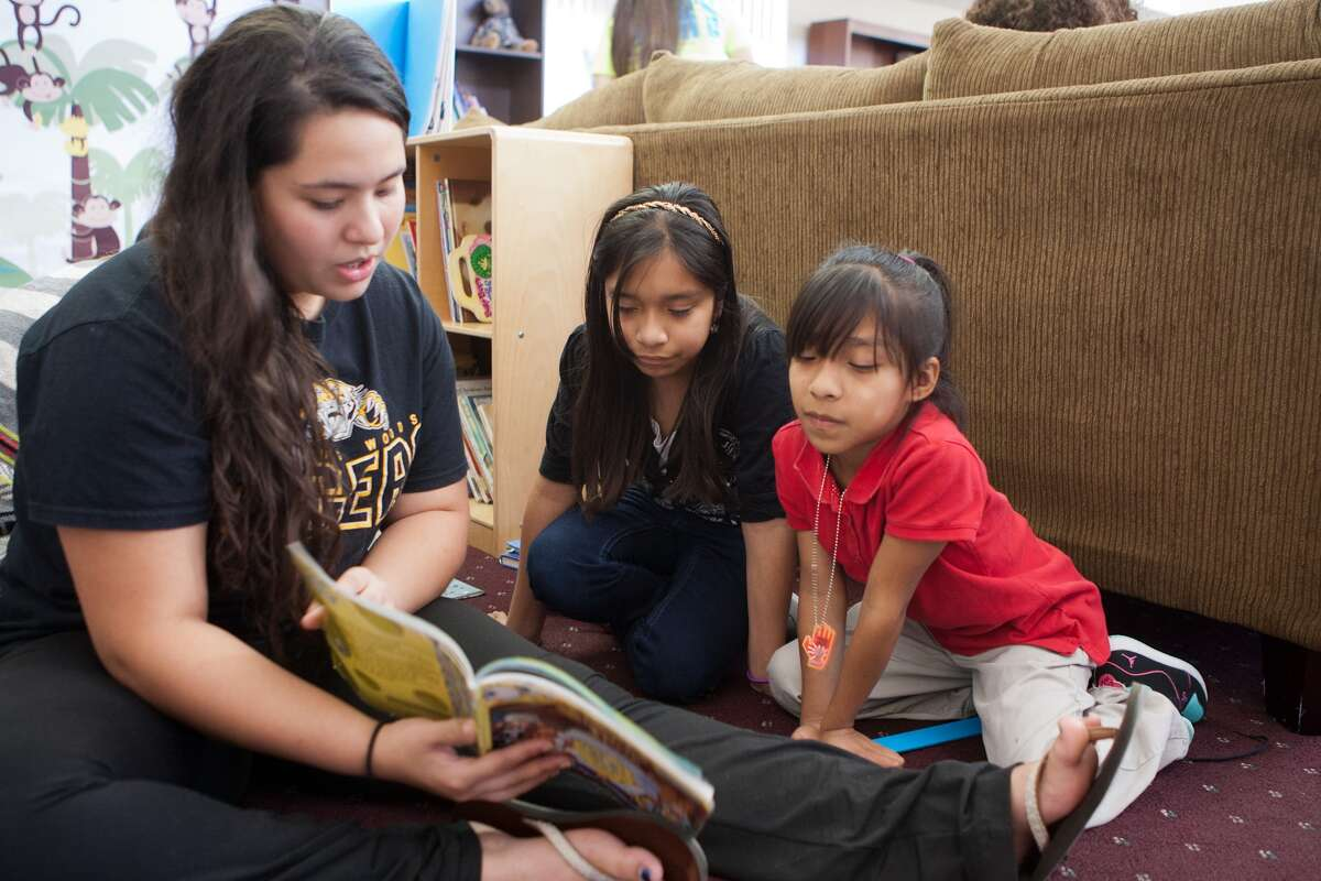 Spring Woods High School volunteer Celeste Gonzalez reads with Gisselle Villamar, 10, and sister Danielle Villamar, 8, at the Kids' Reading Room at Hammerly Walk Apartments. Spring Woods High School volunteer Celeste Gonzalez reads with Gisselle Villamar, 10, and sister Danielle Villamar, 8, at the Kids' Reading Room at Hammerly Walk Apartments.